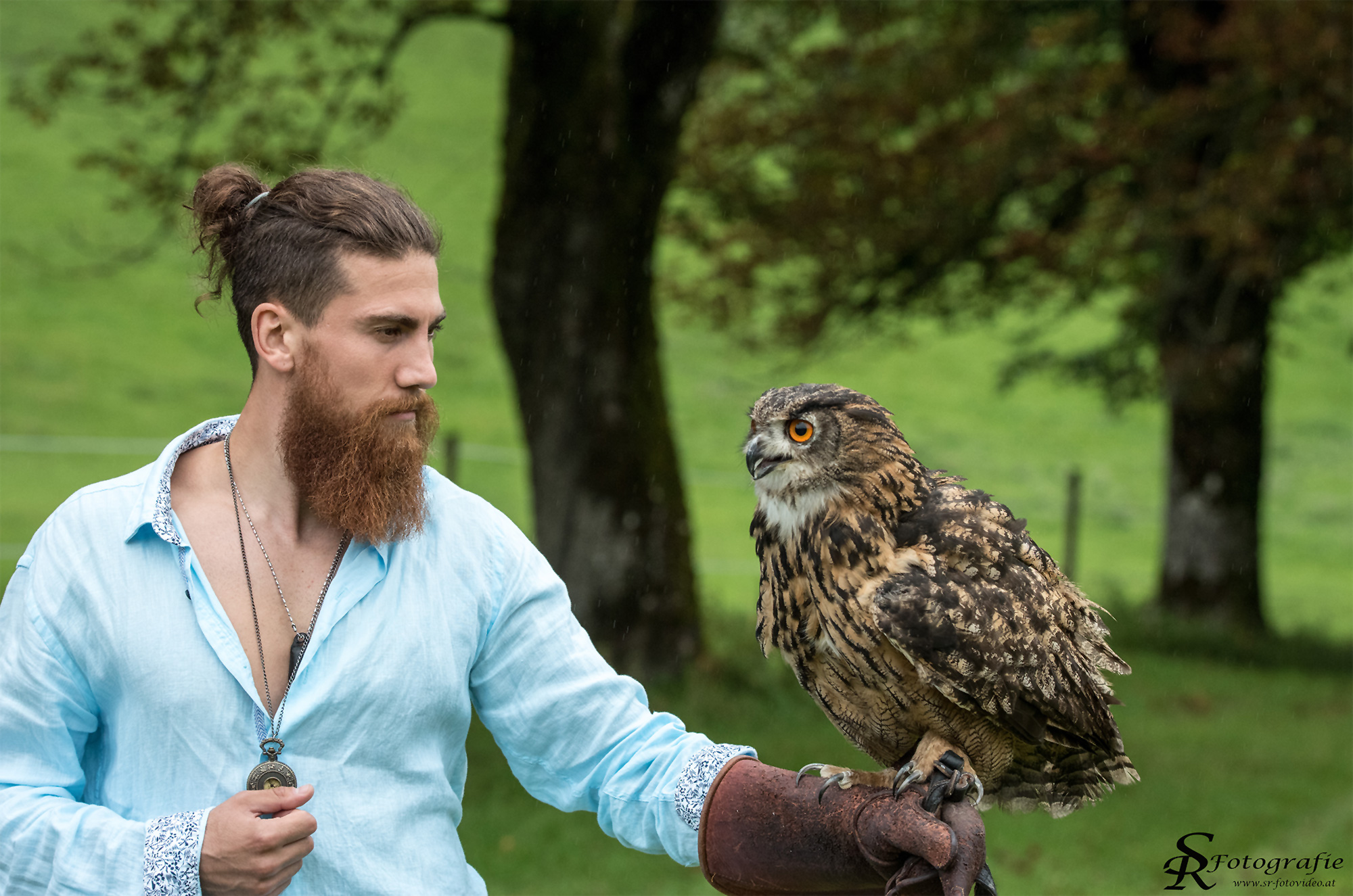Mann mit Greifvogel am Arm